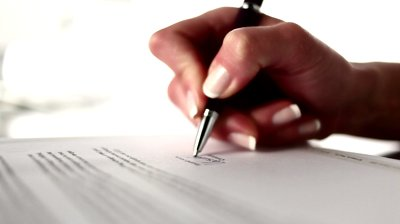 stock-footage-a-female-hand-signing-a-form-close-up-shot